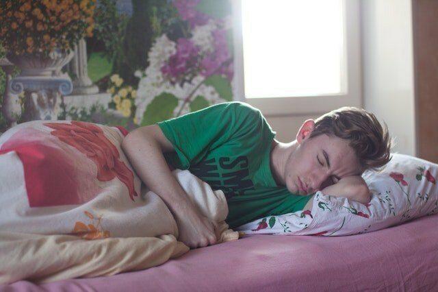 man wearing green printed crew neck shirt while sleeping 296817